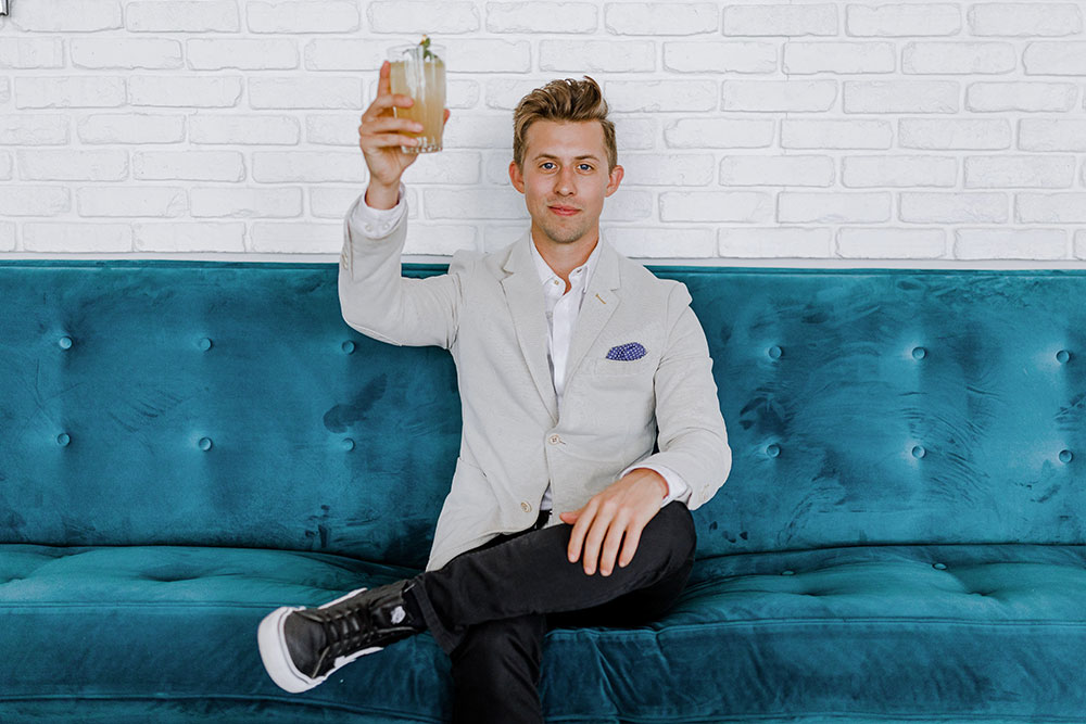 Man in suit raises drinking glass to salute while sitting on blue couch.