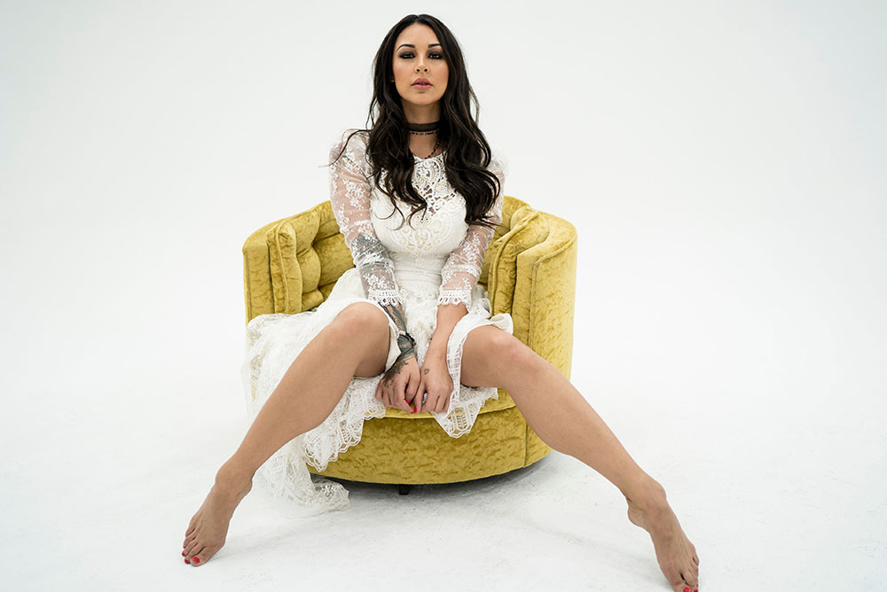 woman wearing white dress sitting on gold chair