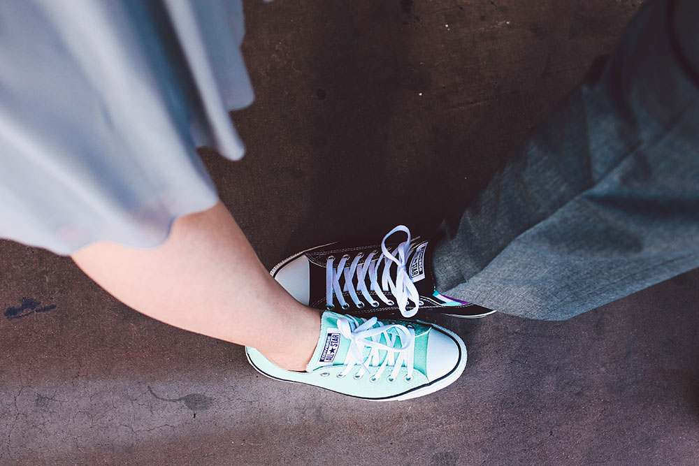 two people comparing converse shoes