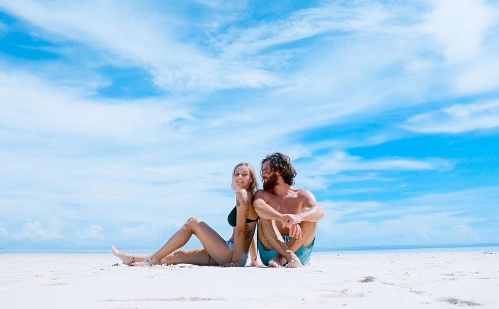 Male and female sitting on beach