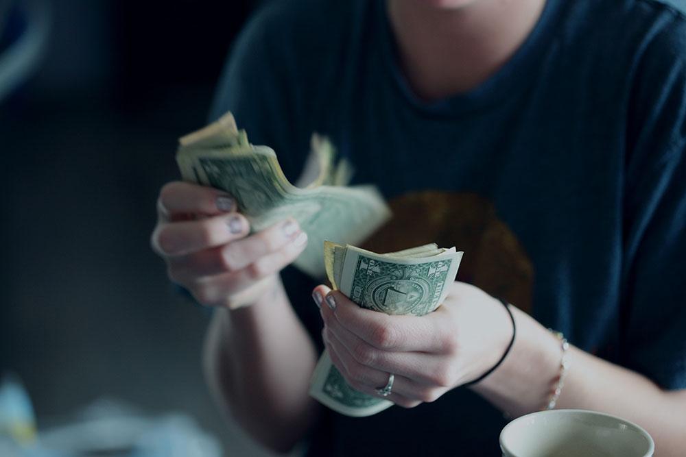 woman counting dollar bills
