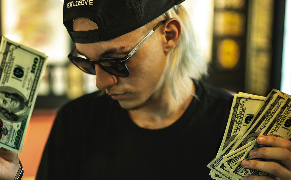 Blonde man with backwards hat and sunglasses holding money