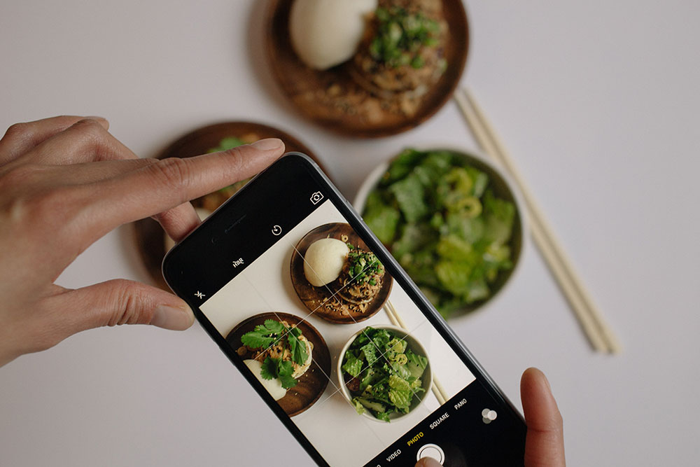 Hands holding phone taking food picture